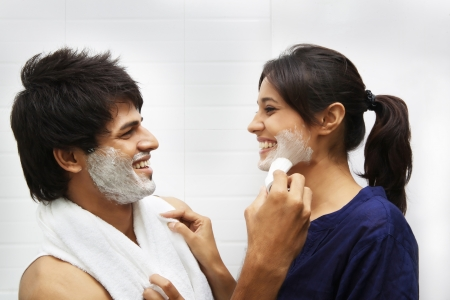 Man applying shaving cream on womans face photo