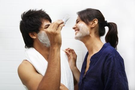 shaving: Man applying shaving cream on womans face Stock Photo