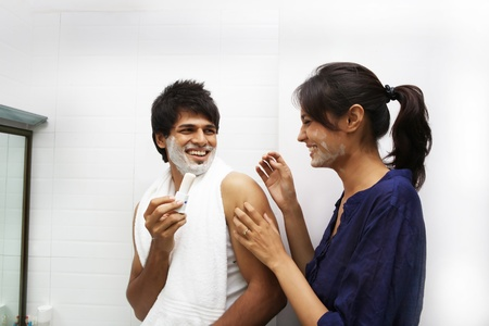Young couple playing with shaving cream photo