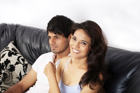 Couple sitting on a couch smiling Stock Photo - 21398591
