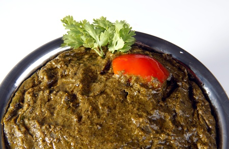 ka: Indian dish sarson ka saag garnished with tomato and coriander leaves