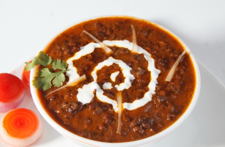 Dal makhani garnished with butter and onions