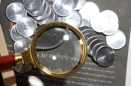 Coins under magnifying glass photo