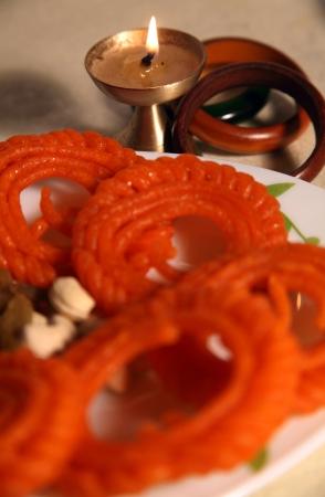 Close-up of Diya and sweets and bangles photo