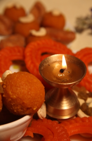 Close-up of Diya,flowers and sweets photo