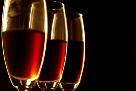 Close-up of three glasses of wine against black background photo