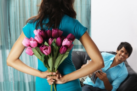 Woman hiding bunch of flowers from man Stock Photo