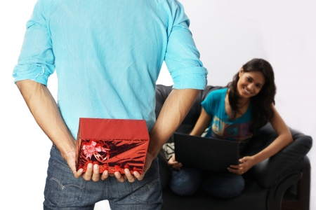 gift behind back: Man hiding gift from woman