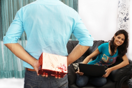 Man hiding gift from woman