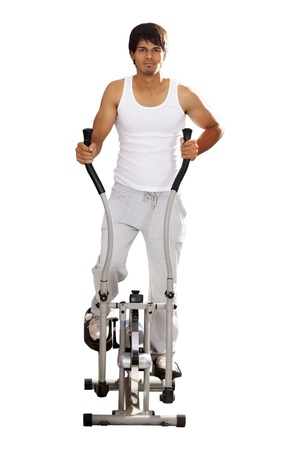 Young man doing exercise on exercise cycle photo