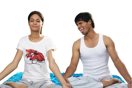 Man teasing woman while doing yoga photo