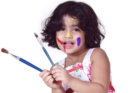 Portrait of a young girl playing with paint brushes photo