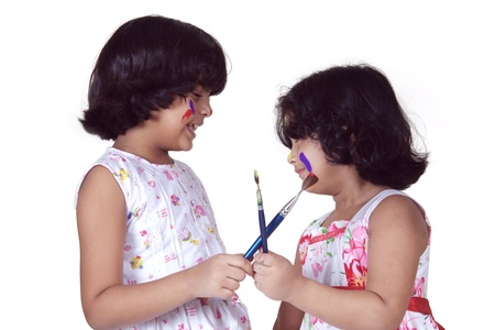 Portrait of two girls playing with paint brushes photo