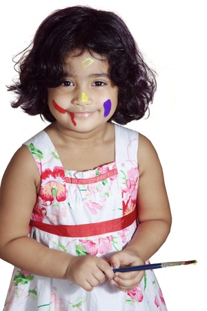 Portrait of a young girl playing with paint brush photo