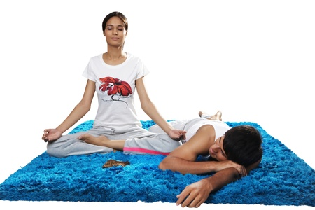 Man sleeping while woman practising yoga photo