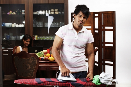 Young man ironing clothes while woman using laptop in background photo