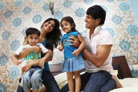 happy families: Los padres juegan con sus hijos en la cama