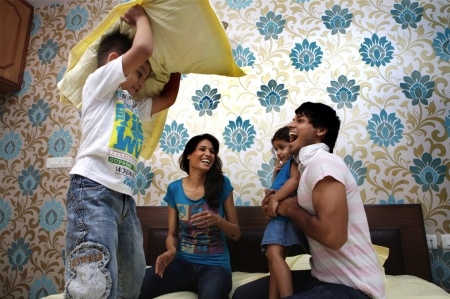 Parents and their kids having pillow fight on bed Standard-Bild