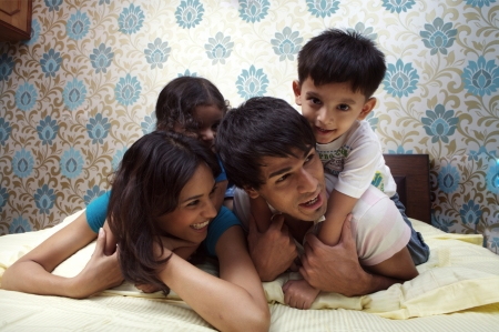 indian couple: Family lying on bed smiling
