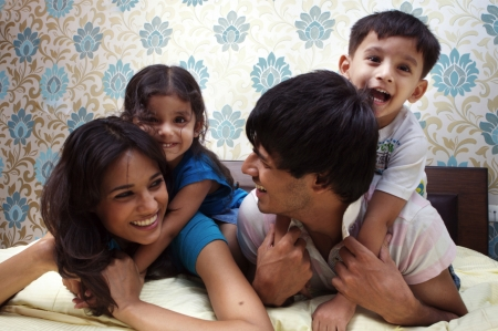 sibling: Family lying on bed smiling