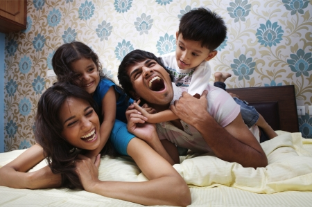 Family lying on bed smiling