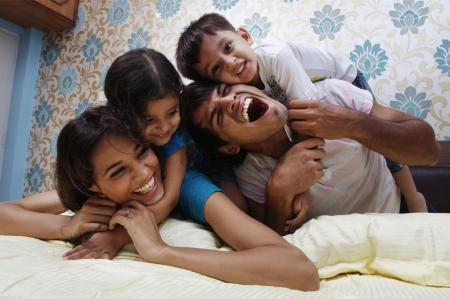 asian indian: Family lying on bed smiling