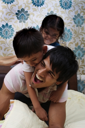 Father and kids playing on bed photo