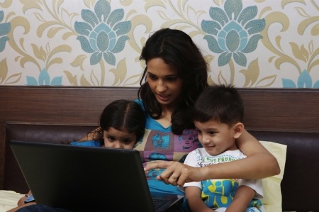 Mother and kids looking at laptop