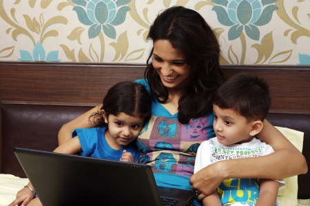 india people: Mother and kids looking at laptop
