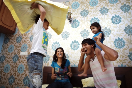 brother sister fight: Parents and their kids having pillow fight on bed Stock Photo