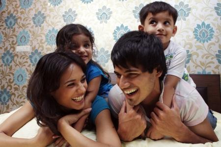 familia abrazo: Familia que miente en la cama sonriendo