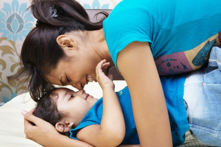 rubbing noses: Happy mother and daughter spending quality time in bed Stock Photo