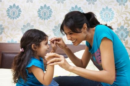Mutter und Tochter spielen auf dem Bett Lizenzfreie Bilder
