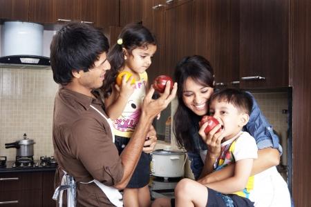 frutas divertidas: Familia que se divierte, comer frutas en la cocina