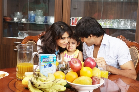 Eltern beruhigt ihre Tochter weinend am Esstisch