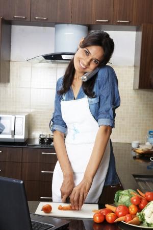 Frau einen Anruf entgegennehmen, während Hacken von Gemüse in der Küche