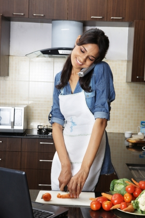 Woman answering a call while chopping vegetables in kitchen Standard-Bild