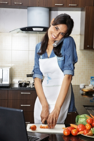 Woman answering a call while chopping vegetables in kitchen photo