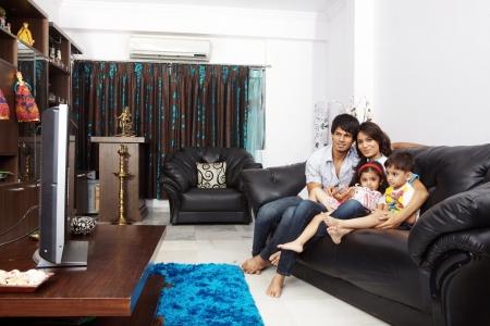 personas mirando: Familia viendo la televisión juntos sentado en un sofá