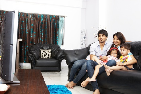 Family watching TV together sitting on a sofa Stock Photo