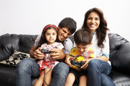 Portrait of parents sitting with their kids and playing video game photo