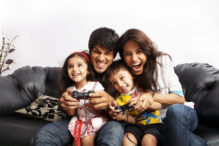 Portrait of parents sitting with their kids and playing video game Stock Photo