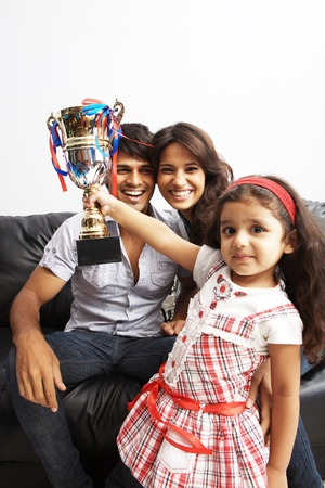 Kid raising a trophy with parents in background