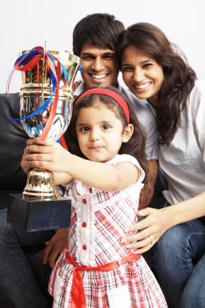 Kid raising a trophy with parents in background photo