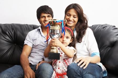 Kid Anheben einer Trophäe mit den Eltern im Hintergrund