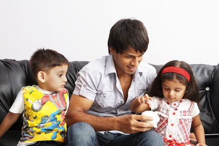 Father and kids putting coins into a piggy bank photo