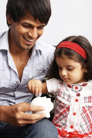Father and daughter putting coins into a piggy bank photo
