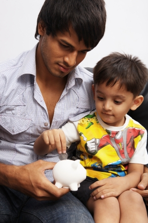 Father and son putting coins into a piggy bank photo