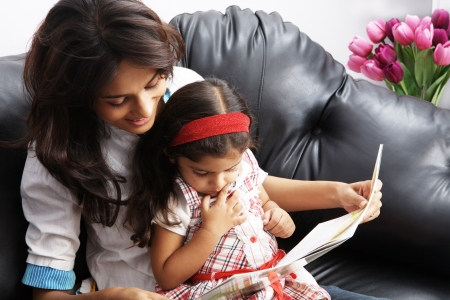 Mother with her daughter sitting on a couch and reading a book