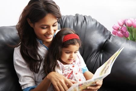 ni�os leyendo: Madre con su hija sentada en un sof? y leer un libro Foto de archivo